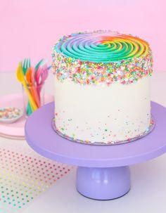 Rainbow swirl cake on purple cake stand.