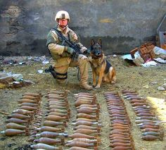 Military working dog and his handler pose for a photo in front of explosives found during a deployment. MWD Benjo retired Nov. 12, 2009. (U.S. Air Force photo)