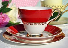 Sutherland fine bone china vintage teacup, saucer and tea plate.  A white china body decorated with a vibrant pillar box red glaze and gold leaf classical border. Gold to the teacup base and handle. Gold gilding around the rims.  The tea plate is 15.5cm diameter.  In excellent condition.  Sutherland. Fine bone china. Staffordshire. England. Made by Hudson and Middleton Ltd, Sutherland Pottery, Longton, Staffordshire Potteries. Date c.1960s.  Perfect for adding a touch of colour to your…