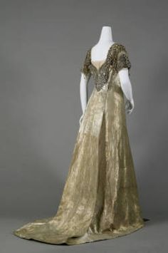 1910. Reville & Rossiter. Dress, evening-style, of twilled silver cloth. Square neck and short sleeves. Bodice trimmed with ornaments of silver bugle beads, seed beads, and rhinestones. Draped light pink tulle at neck and sleeves.