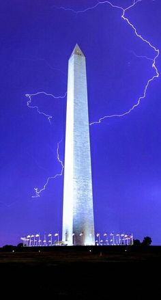 The Washington Monument is lit up against a deep purple sky as a lightning bolt strikes in this impressive photograph