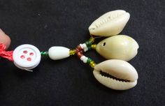 Cowry or cowrie have historically been used as a currency in several parts of the world,but today extensively for jewellery and for other decorative and ceremonial purposes. Cowry shells are viewed as symbols of womanhood.fertility,birth and wealth. In the above 3 pcs of cowry shells are bound together with a cord,glass beads and button to create a decorative shell dangle . These dangles can be used for various craft work ,to decorate bags,gift boxes... Length approx. : 2.25 to 2.5 You will