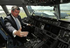 Michael Ryan, a U.S. official with the Pentagon's European Command who is working to increase partnerships with the industry, poses in the cockpit of a Boeing C-17 military transport plane at the Farnborough Airshow 2012 in southern England