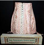 This unworn vintage French pink brocade corset garters and box date from the 1920s. It is made of a paisley leaf patterned pink brocade fabric with a pink lace appliqué trim sewn onto the front top and elastic gussets on the bottom. There are four garter stocking suspenders attached to the bottom, side hooks & eyes and white lacing down the back for closure. This shorter style corset belt is boned with figure supporting stays sewn inside. The corset measures 13 inches long, with a 27 inch…