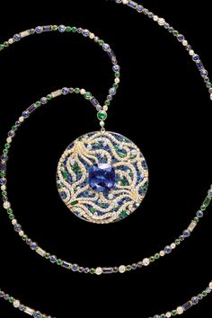 A 15.03-carat cushion-cut tanzanite sits among waves of swirling diamonds while emeralds, tsavorites and sapphires glisten just beneath the surface.