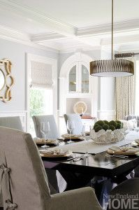 Neutral colors and simple window treatments let the dining room's classic architectural details stand out. The striking antique-bronze ribboned chandelier adds a dose of drama.