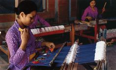 A Balinese weaver works on a backstrap loom with comb.