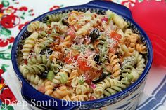 Tri-color rotini pasta salad is paired with red onion, celery, green and red bell pepper, black olives, chopped tomato and dressed with an Italian dressing.