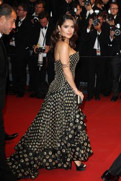 She stuns in a coin-emblazoned, flamenco-inspired gown.   - MarieClaire.com