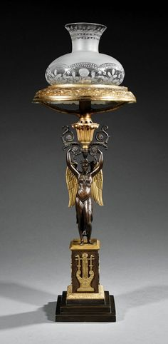 A good Regency gilt and patinated bronze figural Sinumbra (sperm oil) lamp, in the French taste, winged classical fidural standard, embossed font, period cut and etched glass shade