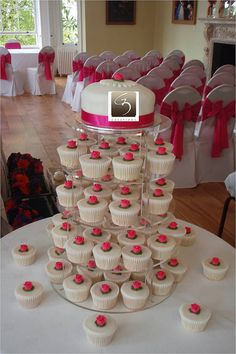 Madagascan vanilla cupcakes frosted with vanilla liquid fondant and fuschia pink roses    Top cake was provided by the client, we just placed another pink rose on top to bring the whole display together!    Set up was at the beautiful venue Pembroke Lodg Check out our wedding ideas at www.CreativeWeddingStyle.com.