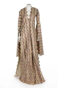 Turkish woman's anteri robe, Ottoman, mid 19th century. richly woven with foliate bands in coral, pink, blue and green silks interspersed with gold stripes, undulating edges with couched gold thread undulations and braid edgings, lined in muslin