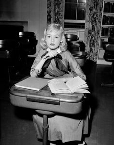 Sandra Dee (age 14) reading at school desk while awaiting the next scene. Until They Sail. March 6, 1957, Hollywood. The young actress makes her film debut with costars Joan Fontaine, Jean Simmons and Paul Newman.Dee plays the baby sister, Evelyn, the only sister who ended up marrying a local boy. Evelyn's role provides comic relief, being the typical 15-going-on-30 teenager and making smarty-pants comments on the ups and downs of her older sisters' love lives.