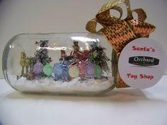 Santa's Orchard Toy Shop -  Materials Needed: Ball Jar (half gallon), 4 miniature presents, miniature toys ( lollipops, rocking horse, nutcrackers, bear), 2 miniature Christmas trees, white styrofoam (for base), fake sparkle sprinkle snow, miniature Christmas string lights, ribbon