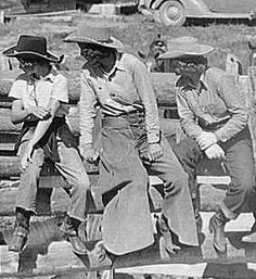 "Cowgirls on a fence -- World War II saw women working and dressing like their male counterparts, and from that time on, ""cowgirl"" attire differed from that of the cowboys only in tailoring details and the orientation of things like flies and plackets."