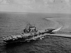 The U.S. Navy aircraft carrier USS Saratoga (CV-3) in 1943/44. The photo was taken from one of her planes of Carrier Air Group 12 (CVG-12), of which many aircraft are visible on deck, Douglas SBD Dauntless dive bombers (aft), Grumman F6F Hellcat fighters (mostly forward), and Grumman TBF Avenger torpedo bombers