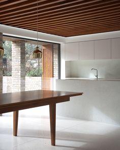 Minimalist white kitchen, large white floor tiles, wood beams