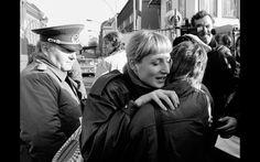 Foto de 10 de novembro de 1989 mostra uma mulher da Alemanha oriental abraçando uma da parte ocidental enquanto um soldado da fronteira observa