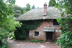 This cottage became a home for a gamekeeper in the century when pheasant shooting became all the rage amongst the idle rich. Manscombe Woods was planted to provide cover for the birds. The cottage was burned down in 1990 and. Arts And Crafts House, Cottage In The Woods, Gazebo, Outdoor Structures, Patio, Devon, Cottages, Outdoor Decor, Plants