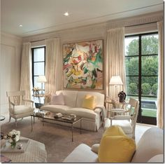 bold colorful artwork, creamy white walls and fabric with pops of color in pillows.