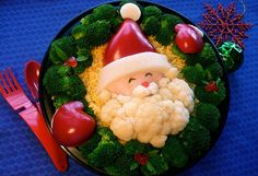 *SANTA BENTO ~ Santa Looking through a Wreath: The bottom layer is cashew chicken ( a meal my family loves) topped with lemon rice. Santa's face is turkey breast, nori eyes, and bell pepper nose. His hat and mittens are bell pepper with jicima accents. I had fun examining peppers to find ones with just the right curves for the hat and mitten shapes I wanted. The wreath is broccoli, and the holly berries are bell pepper with spinach leaves.