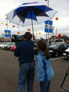 Don Anderson getting a little help during a commercial shoot. He's under her umbrella...ella.