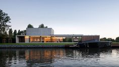 An underground lair modelled on an exclusive nightclub lies below this riverside bachelor pad near Ghent, where the owner has built-in cigar and wine storage, a car lift and a view into the depths of the pool.