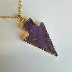 """Amethyst arrowhead necklace This lovely natural stone cut and polished light and dark purple amethyst arrowhead shaped pendent has white line detailes and has a 14k gold plating around it and is attached to a chain that is 20"""" long. Brand new unused and great with your favorite shirt and jeans.  Pendent is 4 1/2 cm long and 3cm wide Jewelry Necklaces"""