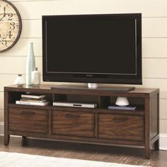 The spacious tabletop and multiple storage options of the Wylder TV Console by Scott Living makes this TV stand the perfect addition to any home. Features classic style and sturdy construction with 3 open shelves and 3 storage drawers.