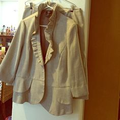 Suit Very cute beige and brown suit the skirt has a little elastic for comfort with 3 ruffles at the slit. The jacket gas a ruffled neck line with a 2 tried ruffle bottom. Sleeves are to the middle of arm past elbow Dresses