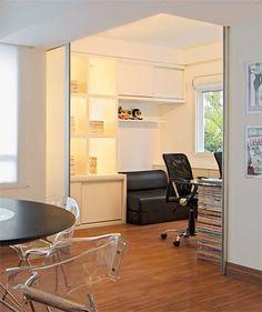 O segundo quarto agora é um escritório, fechado ou aberto para a sala conforme a vontade dos donos – onde haveria paredes, estão duas portas de correr de vidro jateado e alumínio escovado (Grando & Oliveira Indústria e Comércio de Móveis). Na próxima foto, você vê como o escritório fica escondido.