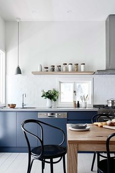 Stunning simple, Scandinavian-style kitchen with blue painted hardware-free cabinetry, open shelving, a rustic farm table, black bistro chairs, and modern pendant lights.
