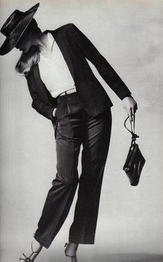 White shirt, cropped black pants, belt, hat, sandals, pouch. Irving Penn, 1980.