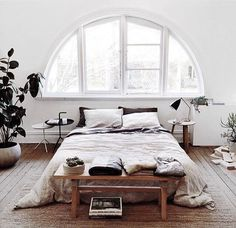 Boho bedroom decor features white light from a half circle window.