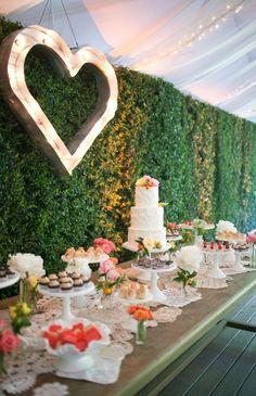 El corazon con las luces por dentro y la mesa para desps de la ceremonia la gente coma en el jardin