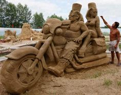 "A park employee fine tunes a sand sculpture called ""The Egyptian Bikers"" at a park in Russia's Siberian city of Krasnoyarsk."