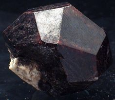 "Pyrope (not to be confused with pyrite) is a type of garnet. It is renowned for its red color (it is always some shade of red or reddish purple) and its name derives from the Greek pyropos which means ""eye of fire"". Some pyropes are such a deep red that they appear almost black."