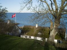 A danish flag next to a typical danish building in Denmark