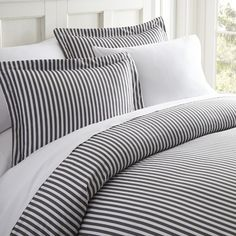 Fusing neutral hues with a timeless stripe pattern, this eye-catching duvet cover set brings versatile style to your cozy bedding ensemble. Crafted from microfiber and showcasing a polyester-fill, it boasts a hypoallergenic design for keeping allergens at bay. Play up this set's nautical influences by adding it to a seafaring master suite ensemble comprised of a navy-upholstered headboard and anchor-embroidered pillows for a touch of texture. Flank the arrangement with a pair of clean-lin...