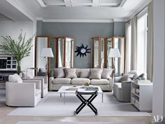 Bespoke folding screens flank a 1950s Line Vautrin mirror in the living room, whose walls are painted in Benjamin Moore's Silver Lake gray.