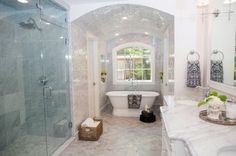 The+former+sitting+room+was+transformed+into+this+lavish+bath+featuring+a+custom+tiled+archway+highlighting+the+pedestal+tub.