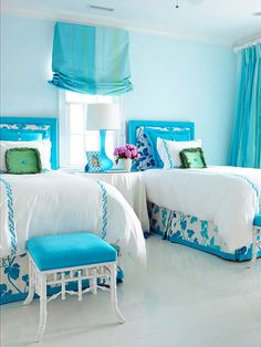 Upholstered headboards and luxurious bedding provide a restful retreat in this guest bedroom. Bold aqua hues used throughout the room in the fabrics and accessories recall the colors of the sea, emphasizing the home's seaside