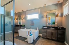 The herringbone tile floors, double sinks, walk-in shower, and free standing bath tub make the master bathroom in this new home stunning. Seen in the Rookwood, a Grand Estates custom home. | Fischer Homes