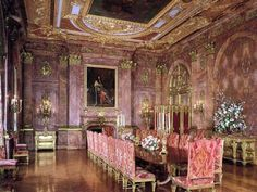 Marble House in Newport, Rhode Island - Dining Room features pink Numidian marble and gilt bronze capitals and trophies. The fireplace is a replica of the one in the Salon d'Hercule at Versailles. The ceiling is decorated painted with a hunting and fishing motif, with an 18th-century French ceiling in the center.