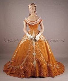 3-piece evening dress, circa 1865-67, Charles Frederick Worth. Orange silk faille, white silk embroidery. Bodice: wide neck with ruche trim. Second bodice (not shown); long fitted sleeves, button front.Skirt; embroidered in white silk with classical motifs, long train (possibly Chinese embroidery). Kent State U Museum.