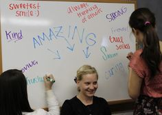 A student sits on a chair in front of a   white board while the others write a positive phrase about them.    They could not peek at what was being written.