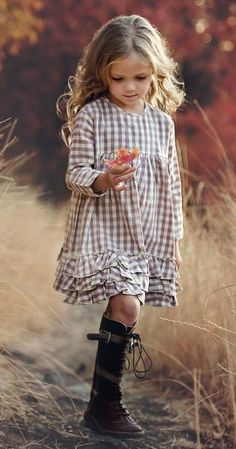 """Greta dress. Three layers of ruffle on the hem gives the dress that extra special vintage look. The model is wearing a size 6 and is 49"""" tall 100% Cotton Coconut Shell Button"""