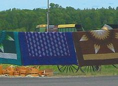 Amish quilts hanging on a line.
