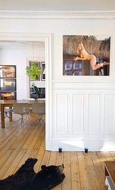 Kig fra stuen mod spisestuen og kontoret. 'Lady G' af Olaf Breuning hænger stilfuldt over de høje paneler.
