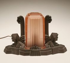 """Art Deco Egyptian Revival boudoir lamp with skyscraper shade. A pair of recumbent sphinxes flank the frosted pink glass architectural shade set upon patinated metal base. 8""""H x 12 1/2""""W. Good condition."""